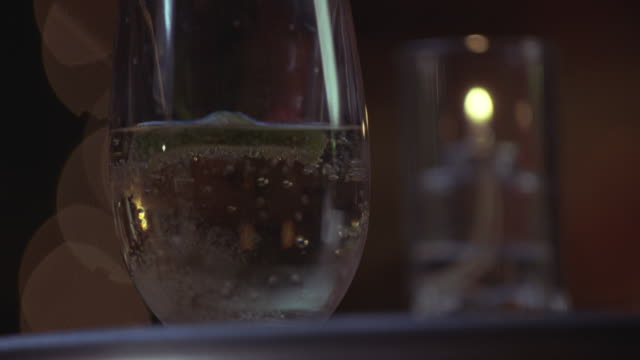 Close angle of a glass with a clear bubbly drink with lime twist. woman's hand drops powder into drink as if drugging it. powder dissolves. could be poison.
