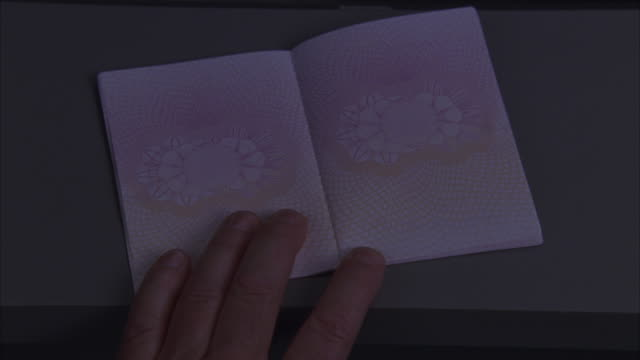 close angle of a hand on a uk united kingdom passport.  the pages open, he stamps the bottom right hand corner. immigration office, visa, id, identification, border crossing. could be airport customs. - uk stock videos & royalty-free footage