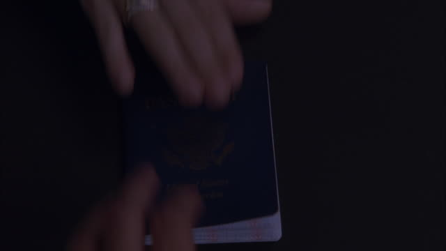 close angle of a hand sliding an united states of america usa passport across a table.  a man's hands opens the passport, stamps in one of the pages, and hands it back.  immigration office, visa, id, identification, border crossing. could be airport custo