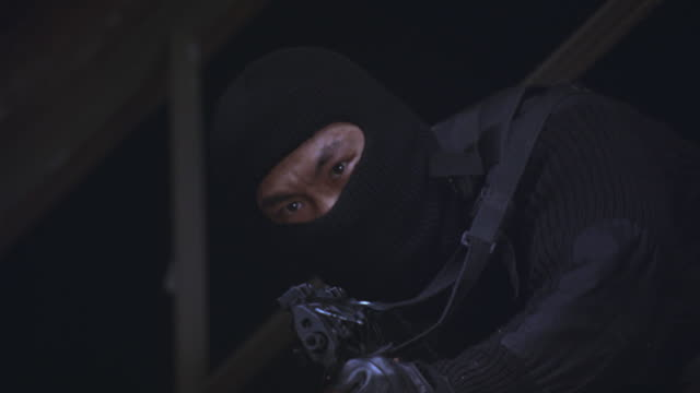 close angle of a masked guerrilla soldier, assassin, or terrorist hanging out of a window.  shoots machine gun.  gunfire rips bullet holes around him and he slumps dead.  stunt. - assassination stock videos and b-roll footage