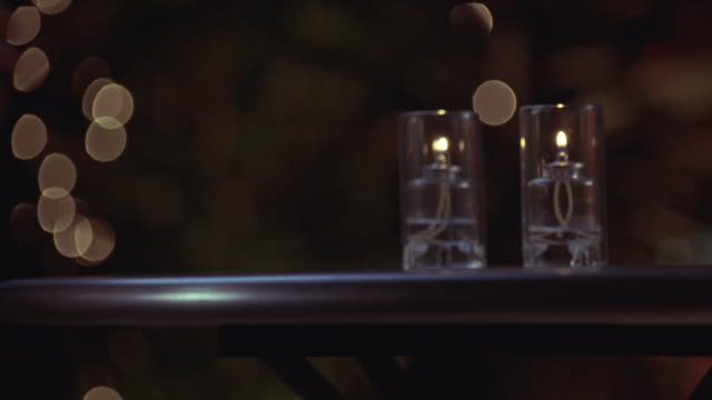 Close angle of a table with two oil candles. man's hand puts down clear bubbly drink in a glass with lime twist down. picks up glass again and puts it down again. could be alcoholic drink or seltzer. lighting in bg suggests patio or poolside.
