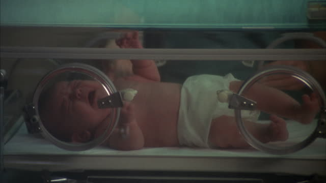 Close angle of baby in white diaper squirming and crying in hospital incubator.