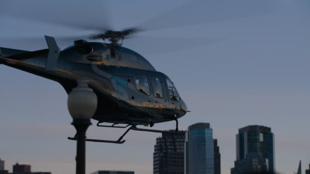 close angle of helicopter landing on helipad in new york city. high rise office buildings visible in bg. - helipad stock videos & royalty-free footage
