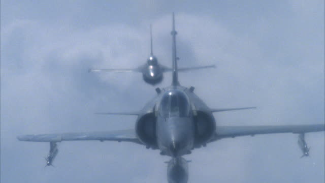 close angle of kfir being followed by f-16 fighter jet both moving towards camera. f-16 does barrel roll to left off bottom of screen, f-16 comes back on screen and then does right barrel roll off bottom of screen. - fighter stock videos & royalty-free footage