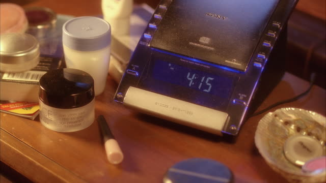 close angle of nightstand with clock. makeup. lights turn off. - changing clock stock videos and b-roll footage