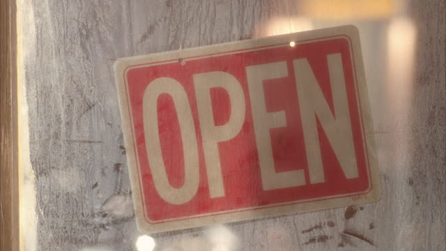 Close angle of open sign in dirty or dusty window.