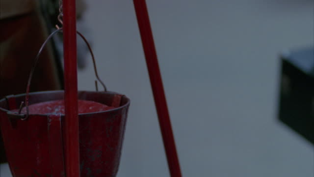 close angle of red bucket of salvation army donations during christmas time. see pedestrains walk by as one person puts money in bucket. pans left to man playing trumpet or instrument. - bucket stock videos & royalty-free footage