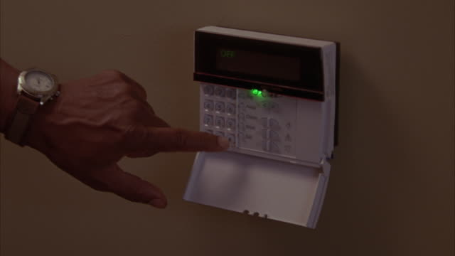 Close angle of security alarm key pad. man's hand pushes buttons to set it to armed.