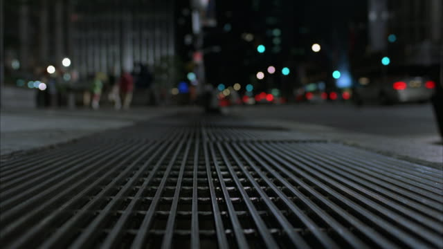 Close angle of street vent or grill. see blurred movement of people walking down sidewalk on left and passing traffic on right.