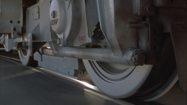 vídeos de stock e filmes b-roll de close angle of trolley wheels on railroad tracks, pov mounted on side of train. train tracks are laid in cement in beginning and then are over railroad ties. see other parts from undercarriage. - chassi