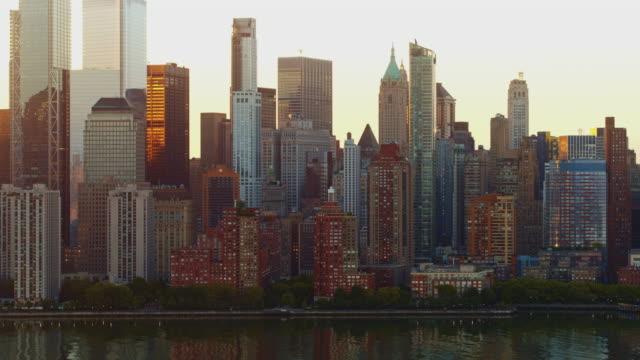 日の出時にハドソン川からマンハッタンダウンタウンの近くの景色。映画のパンカメラモーションを持つ空中映像。 - 連続するイメージ点の映像素材/bロール