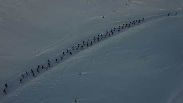 close dronefootage of peloton of skiiers racing up hill - close - プロトン点の映像素材/bロール