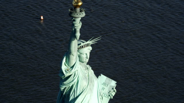 close flight past the statue of liberty above autumn trees on liberty island. shot in 2011. - statue of liberty new york city stock videos & royalty-free footage