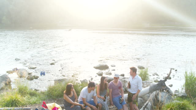 close flyover of people sitting by the river isar - grigliare video stock e b–roll