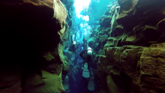 close in view of two scuba divers swimming through the narrow section of the silfra fissure between the underwater cliffs in thingvellir national park iceland. - tectonic stock videos & royalty-free footage