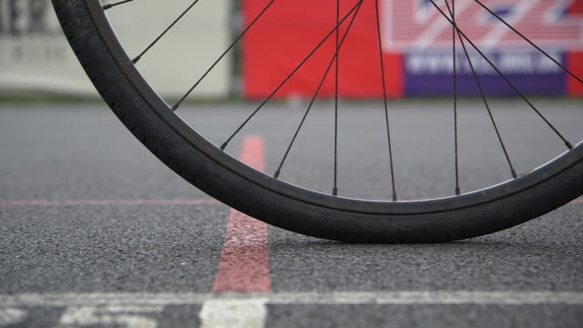 close, low-level shot of the front wheel of a bike being pushed towards and away from a start line at a velodrome, uk. - cycling stock videos & royalty-free footage