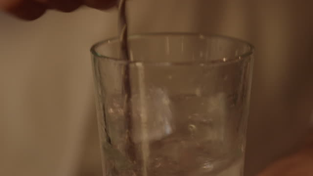 Close pan up of a bartender mixing vermouth in a glass with ice