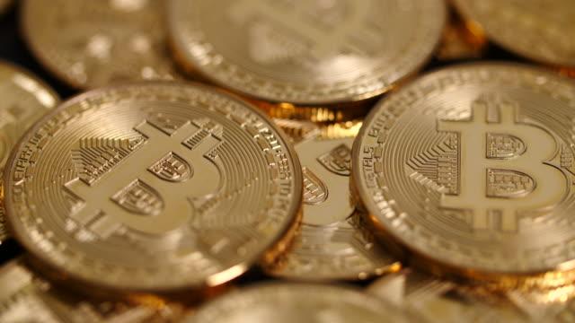 close panning shot across a pile of bitcoins. - blockchain video stock e b–roll