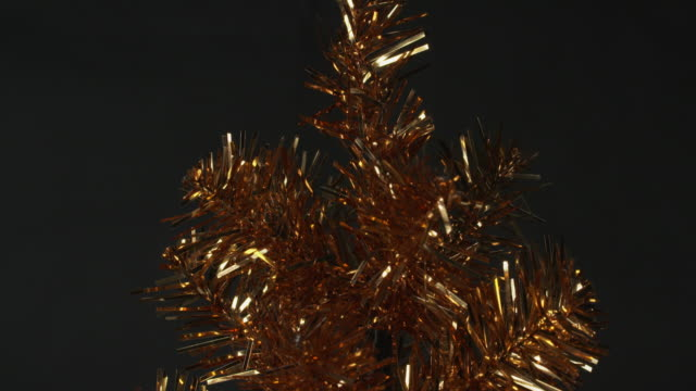 close pull focus on a gold tinsel christmas tree. - tinsel stock videos & royalty-free footage