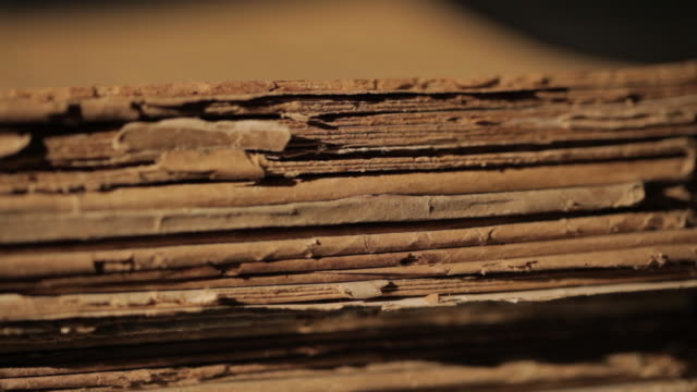 Close shot across a stack of old manuscripts.