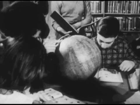 vídeos y material grabado en eventos de stock de / close shot as someone places a snow / inuit box display on a shelf / children at table play with globe and read books / shots of other students and... - 1951