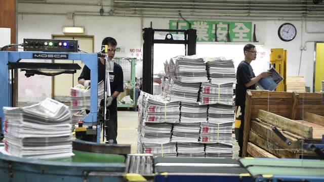 Close shot logo for the Apple Daily newspaper is displayed on the top corner of the newspaper Medium shot copies of the Apple Daily newspaper sit...