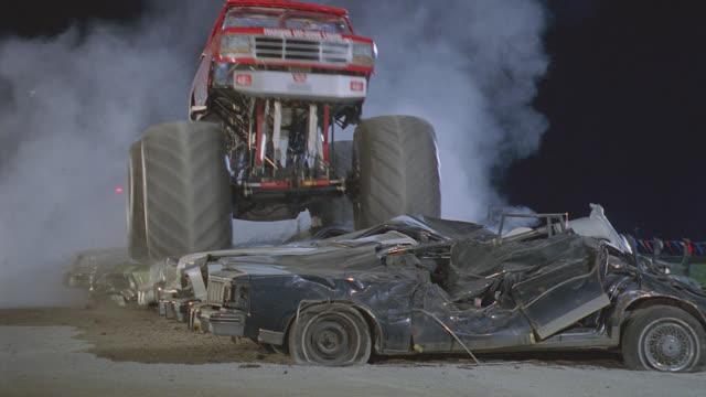 n/x close shot monster trucks to camera, crush cars - 潰された点の映像素材/bロール