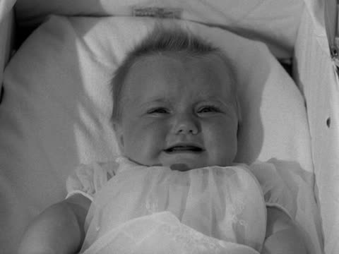 close shot of a baby in a carry cot starting to cry - bedclothes stock videos & royalty-free footage