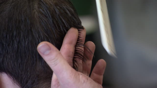 Close shot of a barber cutting a customers hair