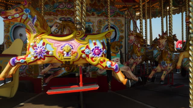 close shot of a beautifully decorated carousel on brighton's palace pier. - 回転遊具点の映像素材/bロール