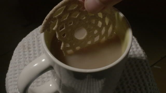Close shot of a biscuit being dipped into a cup of tea.