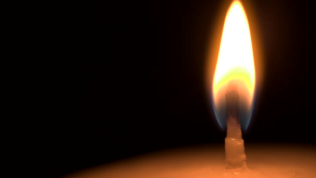 Close shot of a burning candle wick.
