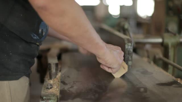close shot of a carpenter using a band saw to cut a length of wood. - menschliche gliedmaßen stock-videos und b-roll-filmmaterial