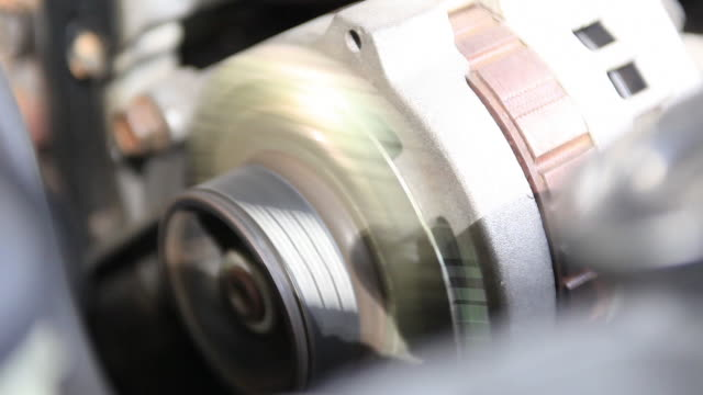 Close shot of a cars alternator spinning in motion.