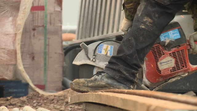 Close shot of a construction worker using an angle grinder on a building site