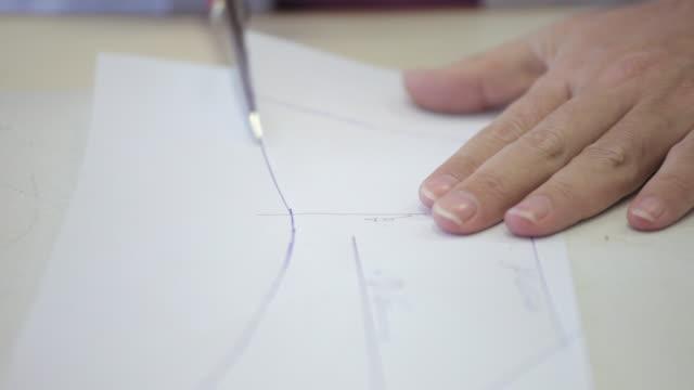 vídeos de stock, filmes e b-roll de close shot of a dressmaker cutting out a dress pattern. - tesoura