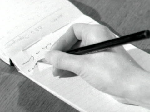 Close shot of a hand writing shorthand on a notepad with a pencil