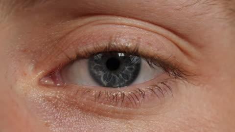 close shot of a human eye blinking. - blinking stock videos & royalty-free footage