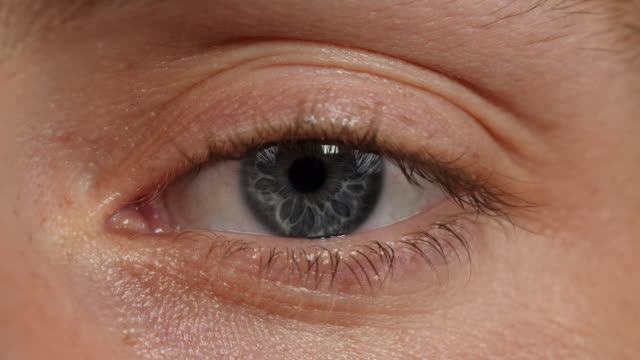 close shot of a human eye blinking. - eyeball stock videos and b-roll footage