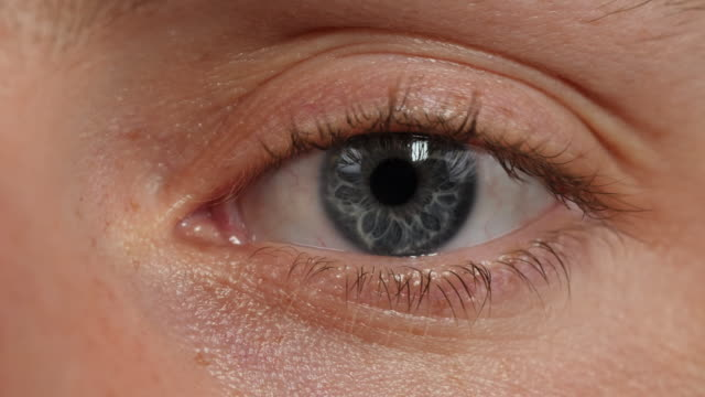 close shot of a human eye blinking. - blue eyes stock videos and b-roll footage