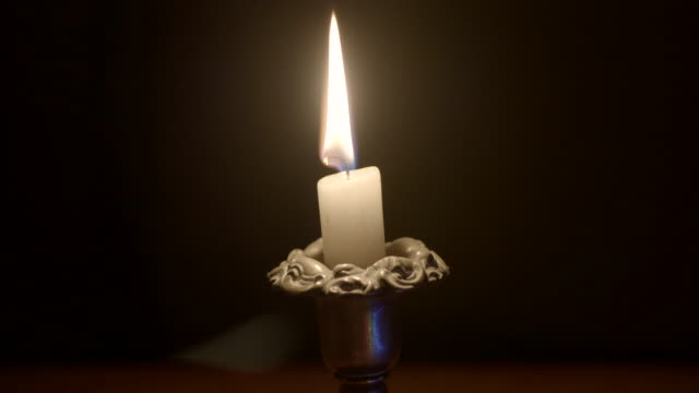 close shot of a lit candle. - candlelight stock videos & royalty-free footage