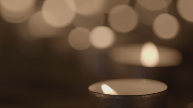 close shot of a lit tea light. - candle stock videos and b-roll footage