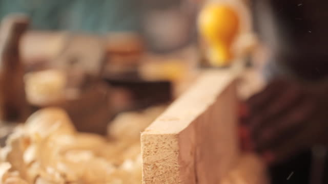 Close shot of a man planing a plank of wood.