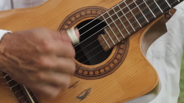 Close shot of a man playing a guitar.
