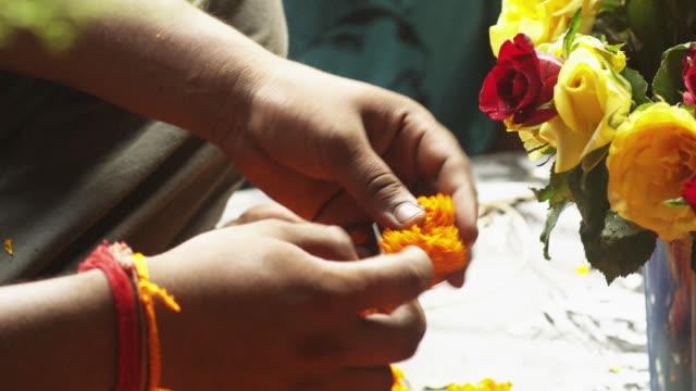 Close shot of a man preparing a garland of marigolds in Guwahati in Assam, India.