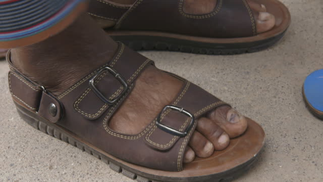 Close shot of a man removing his sandals before entering a mosque.