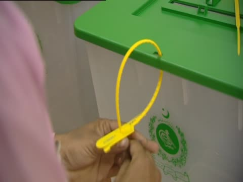 close shot of a man tying ballot box with cable ties at a polling station in karachi - cable box stock videos & royalty-free footage