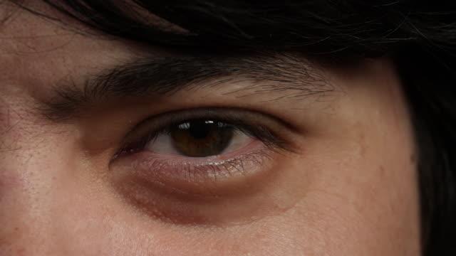 close shot of a man's left eye. - man blinking stock videos & royalty-free footage