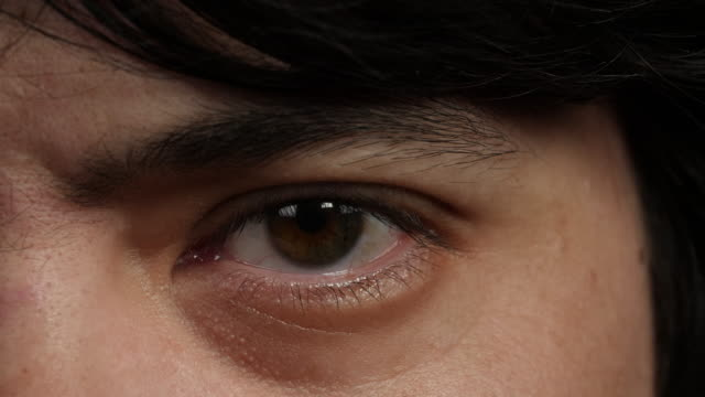 close shot of a man's left eye. - brown eyes stock videos & royalty-free footage