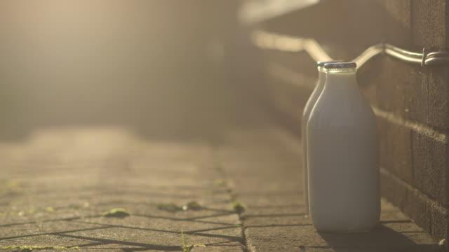 Close shot of a milkman placing milk bottles on a doorstep.